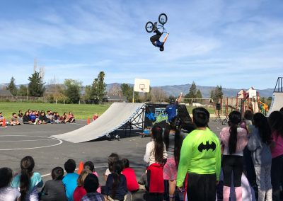 Crowd of students and teachers on College School District playground watching a BMX professional perform a backward flip off a tall launch ramp.