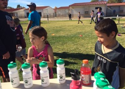 Two elementary students standing in front of table of water bottles at the Santa Ynez School Fun Run 2015.