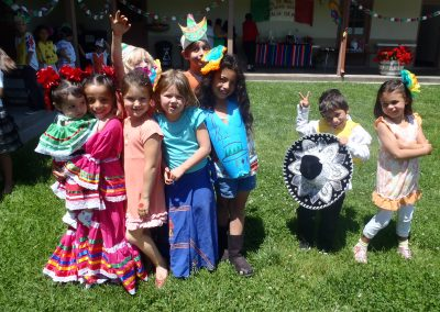 Seven College School students and one student holding a young child celebrating Cinco de Mayo in colorful dress and hats in school courtyard.
